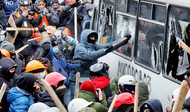 19 січня, друга хвиля протистояння, міліцейські автобуси на Грушевського трощать мітингувальники. фото Reuters
